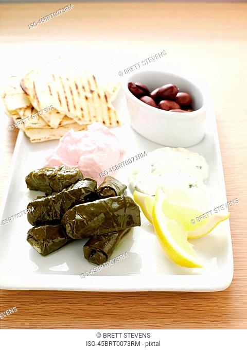 Plate of rolls, lemon, olives and bread