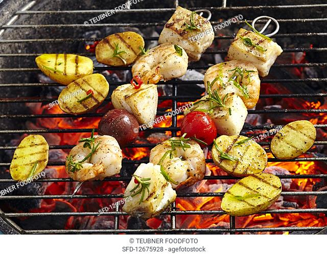 Cod and prawn skewers with grilled potatoes on a coal-fired grill