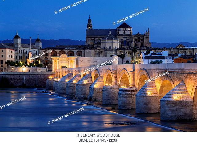Illuminated arches of urban bridge in Cordoba cityscape, Andalusia, Spain