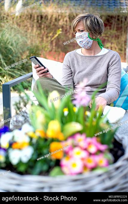 Woman wearing face mask using smart phone while sitting at patio during lockdown