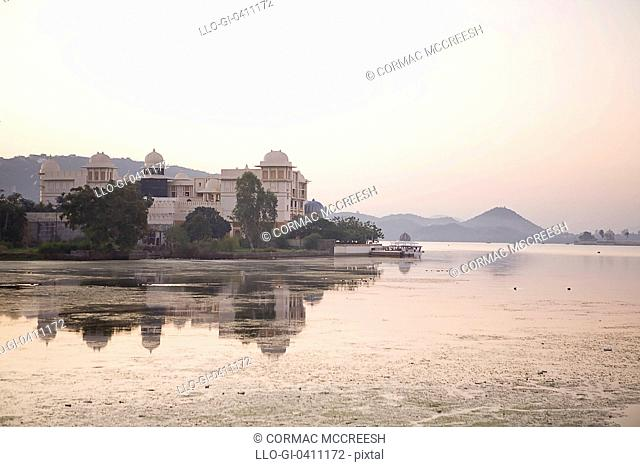 Image of the City Palace and it's reflection in Lake Pichola at dawn in Udaipur, Rajasthan, India
