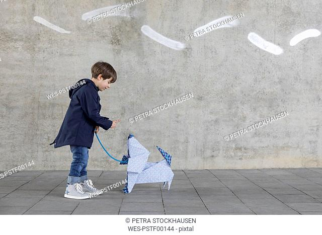 Little boy exercising with origami dog