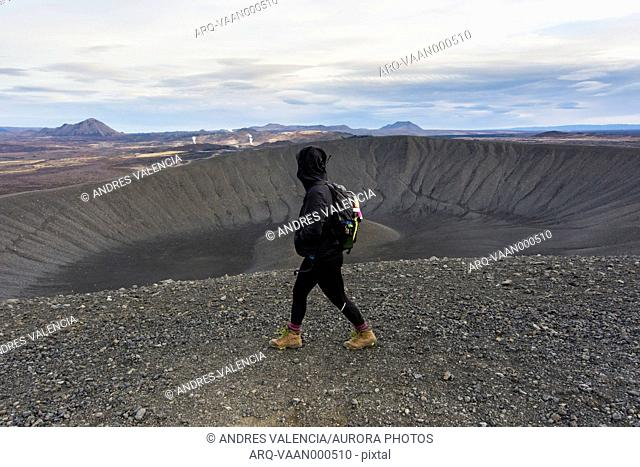 A young woman dressed in black and wearing boots walks along the ridge of the Hverfjall crater with steam rising in the volcanic background