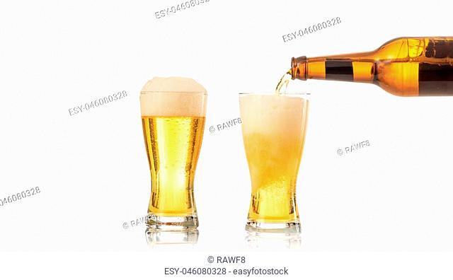 Bottle of beer pouring beer in a glass on white background