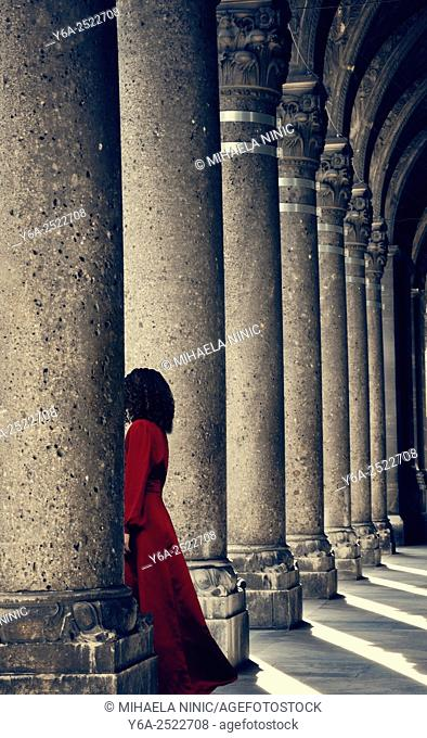 Mysterious woman in red dress behind column