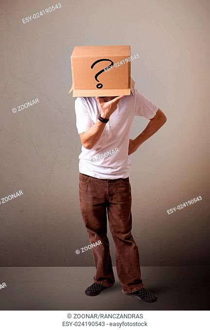 Young man gesturing with a cardboard box on his head with question mark