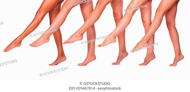 Beautiful legs. Close-up of five beautiful women stretching out their perfect legs while standing close to each other and against white background