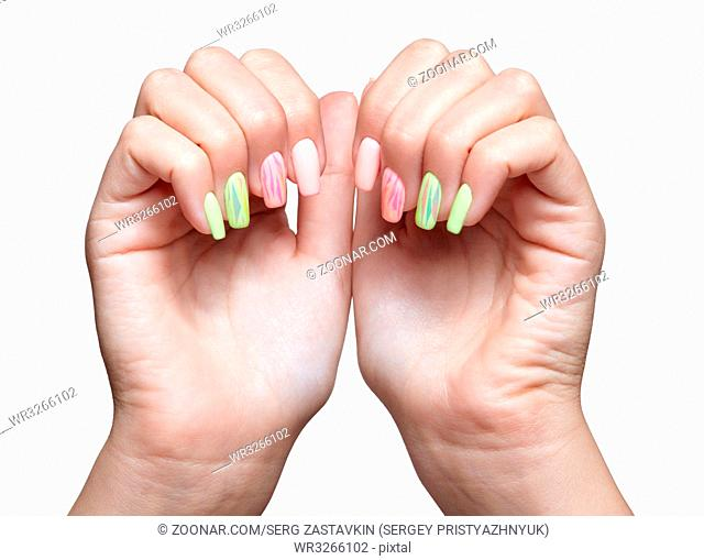 Female hands with woman's professional natursl pink and green nails manicure isolated on white