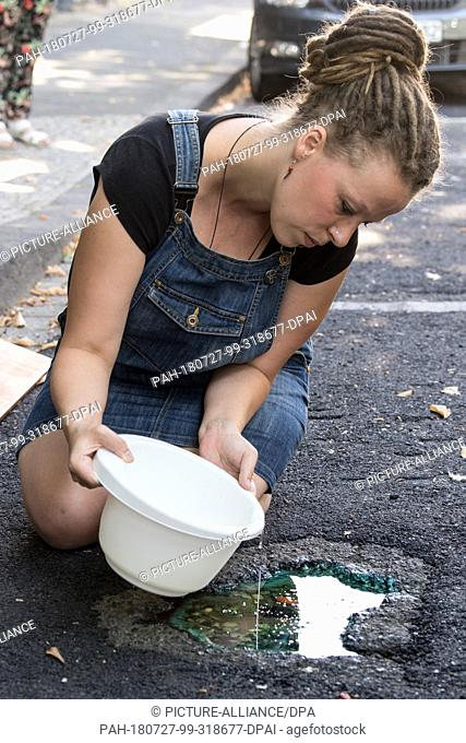 27 June 2018, Germany, Mönchengladbach: The artist Maren Dörwaldt fills synthetic resin into a pothole transformed into a work of art
