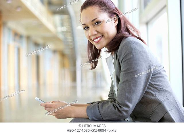 Young businesswoman holding mobile phone in hallway