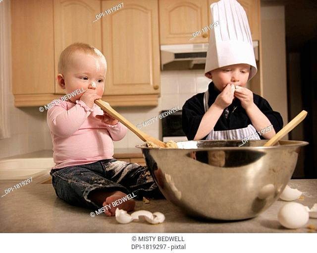 Two kids making cookie dough