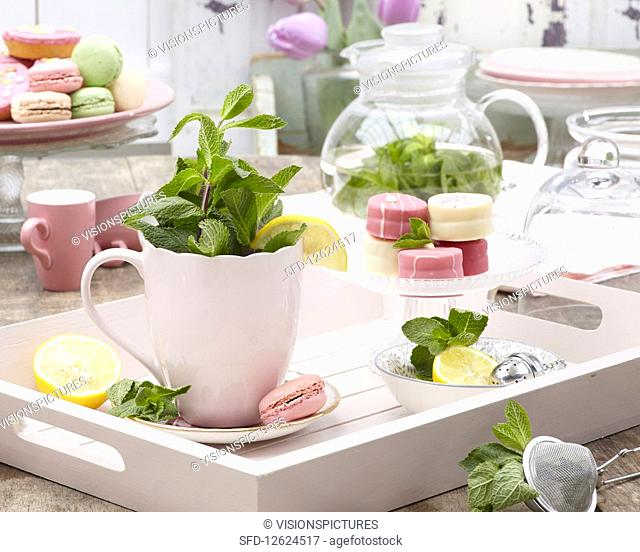A cup of mint tea petit fours on a glass cake stand on a wooden tray