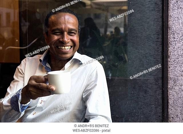 Portrait of laughing man in a cafe with cup of coffee