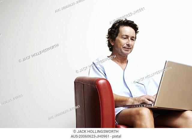 Mature man sitting in an armchair and using a laptop