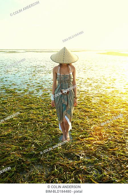 Pacific Islander woman standing in rice paddy