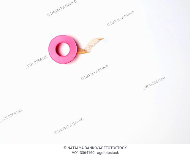 medical textile adhesive plaster for skin in a twisted, pink plastic packaging on a white background