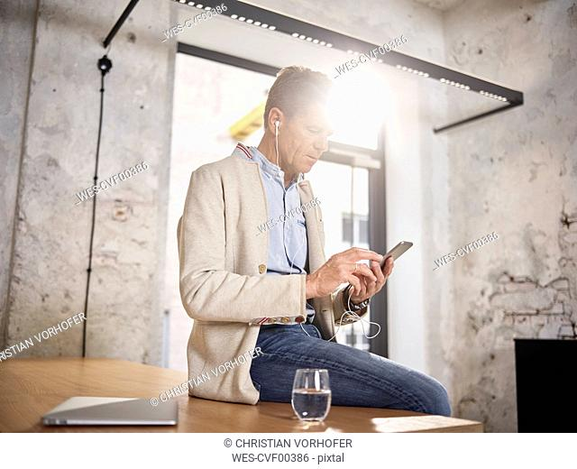 Businessman sitting on desk in office with cell phone and earbuds