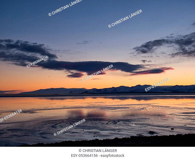 Silent sea in Iceland in winter with sunset behind the mountains