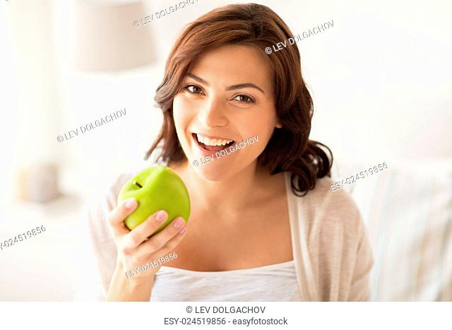 healthy eating, diet and people concept - smiling young woman with green apple at home