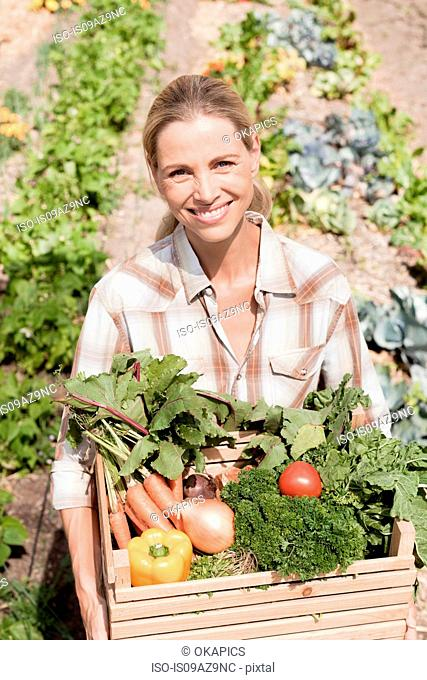 Portrait of mature woman in garden, holding crate of fresh vegetables