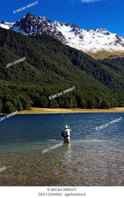 A man practices fly fishing at Mavora Lake; Mavora, Southland, New Zealand