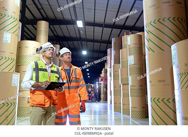 Workers using digital tablet in paper storage area of port