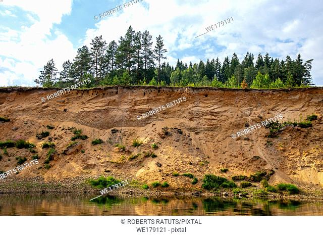 Landscape with cliff near the river Gauja, blue sky and trees. Gauja is the longest river in Latvia, which is located only in the territory of Latvia