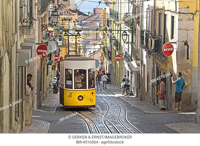 Tram, gondola passing through narrow street, Lisbon, Portugal