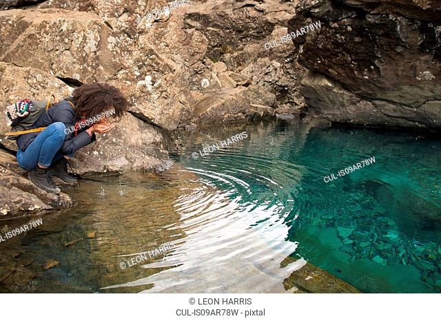 Woman drinking water from cupped hands, Fairy Pools, Isle of Skye, Hebrides, Scotland