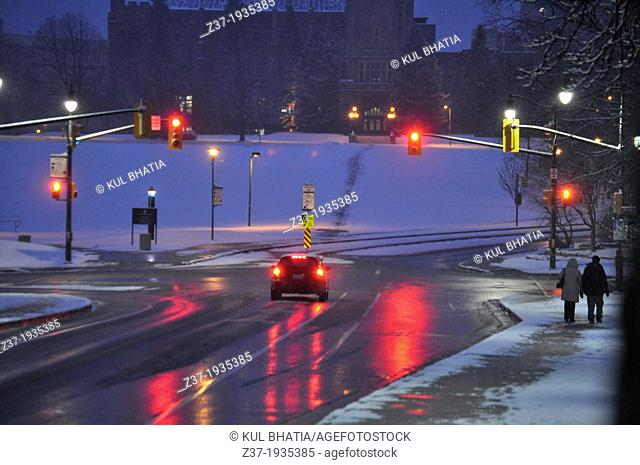 A car stops at a red light on a snowy morning in Ontario, Canada. Fresh snow covers the hill, but salt has been spread to melt the snow on the road