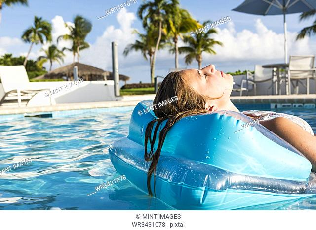 13 year old girl relaxing in a floatie in a pool