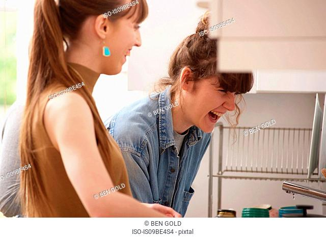 Friends laughing in kitchen