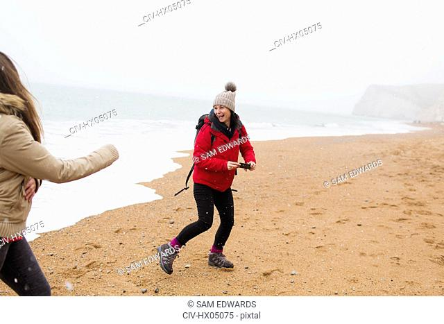 Playful mother and daughter on winter ocean beach