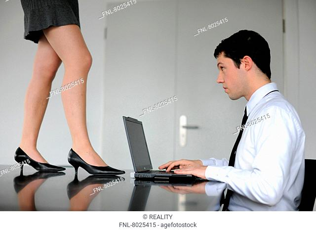 Sexual harrassment at work: A woman in a short dress is distracting a businessman from work