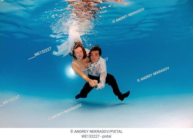 Bridal couple, underwater wedding in pool