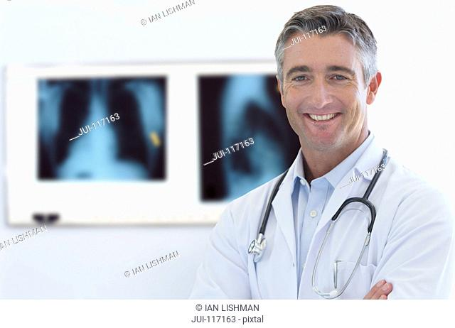 Portrait Of Male Hospital Doctor Standing By X-Rays
