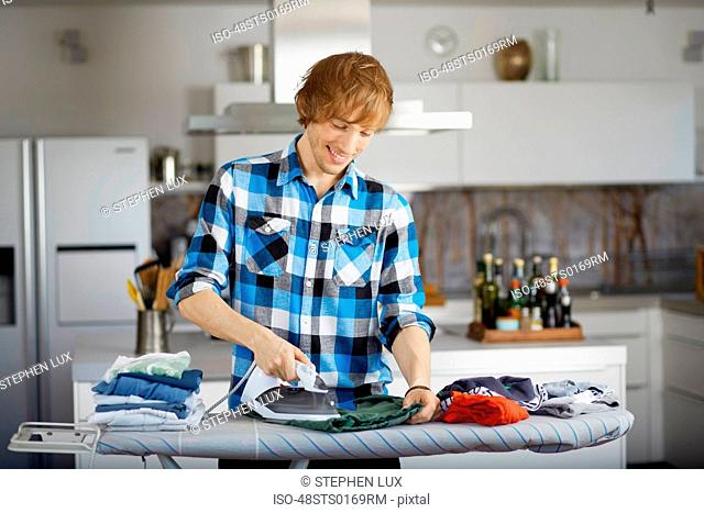 Father ironing child?s clothes