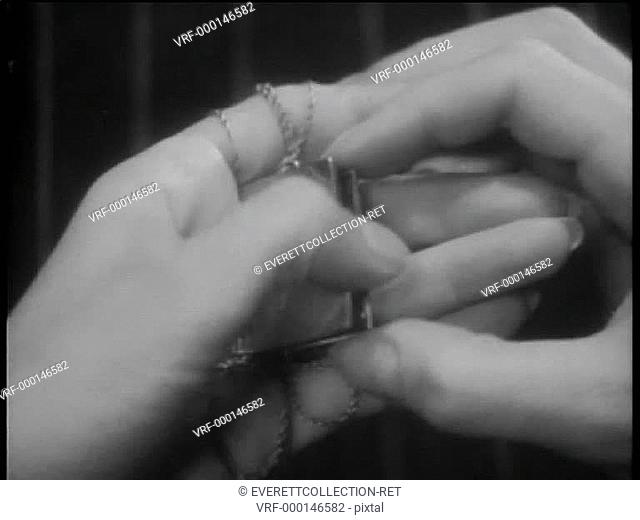 Close-up of hands opening locket with note inside
