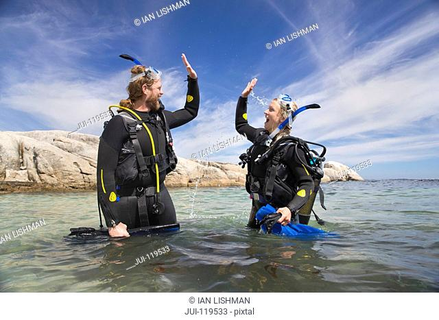 Happy scuba diver couple in ocean celebrating dive with a high five