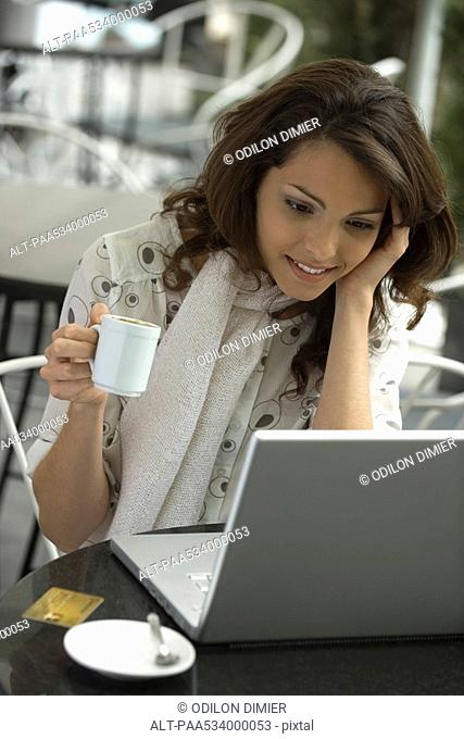 Young woman using laptop in cafe, coffee cup in hand, high angle view