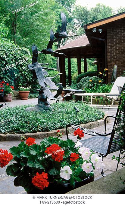 Flying Geese sculpture, Geraniums (Pelargonium hortorum ), Box (Buxus sempervirens), Periwinckle (Vinca minor)
