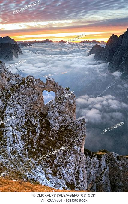 Colorful sunrise in front of the heart shaped arch of stone in the Pale of the Balconies, Pala group, Dolomites. Europe, Italy, Veneto, Agordino