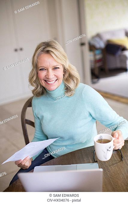 Portrait smiling, confident female freelancer working at laptop and drinking tea at home