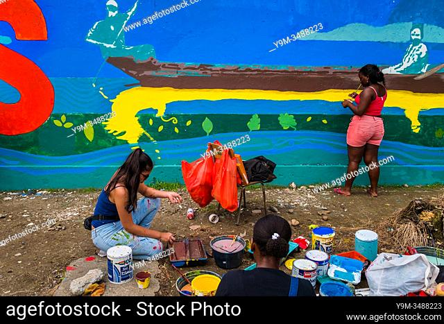Afro-Colombian female students paint a society and environment-related mural on a school wall in Quibdó, Colombia, 5 October 2019
