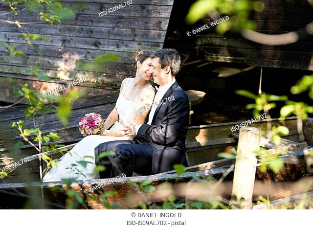 Bride and bridegroom sitting in rowing boat on river