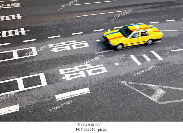 A yellow taxi on a highway