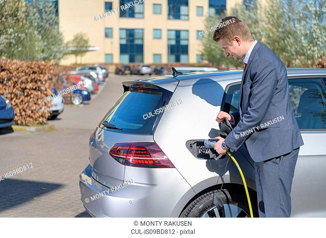 Businessman charging electric car at charging point in business park