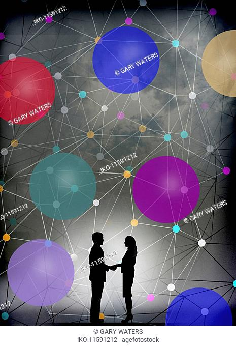Businessman and businesswoman shaking hands in front of network connection pattern