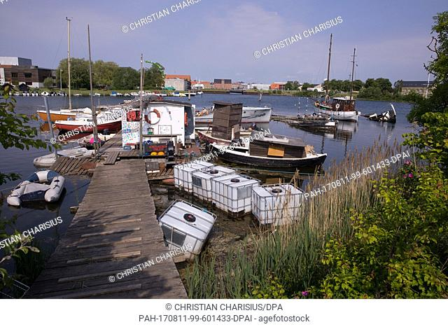 Small houseboats and other watercraft photographed at a wide section of canal near Freetown Christiania in the Christianshavn district of Copenhagen, Denmark