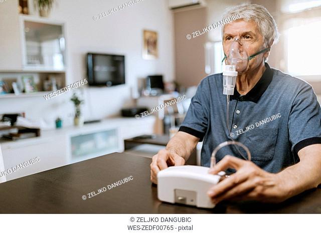 Senior man using inhaler at home